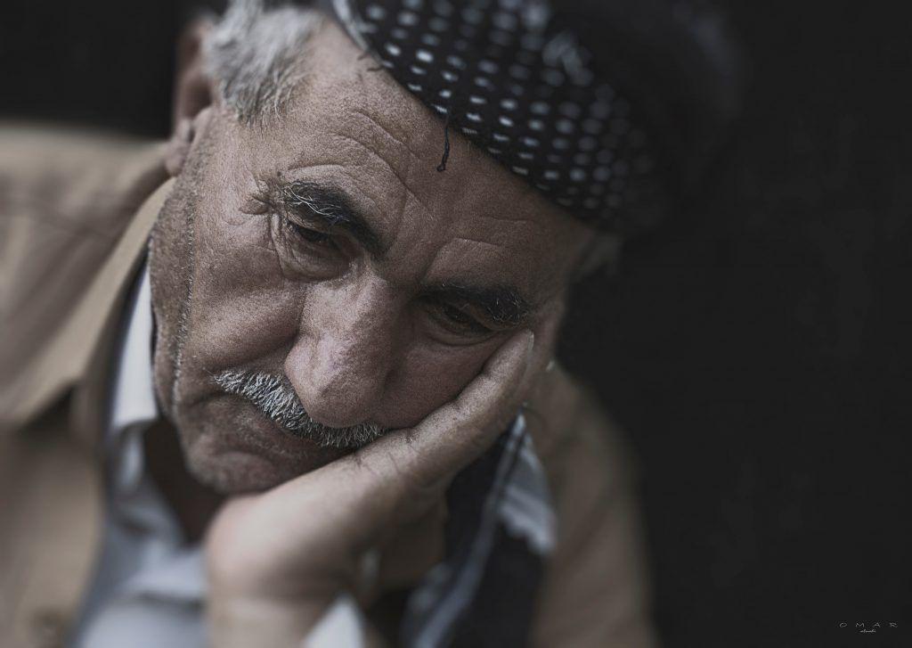 Oude verdrietige man leunend op hand