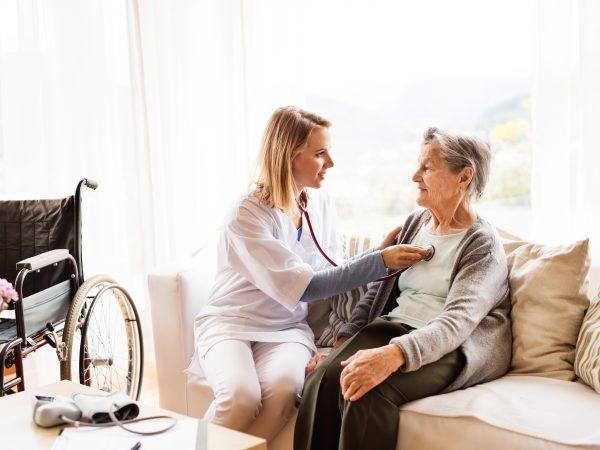 Oudere vrouw met verpleegster thuis