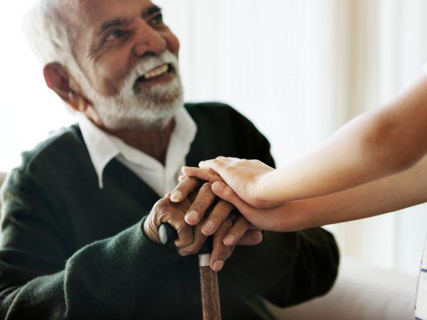 Oudere man met wandelstok met helpende hand