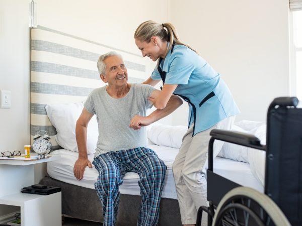 Oudere man wordt uit bed geholpen door verpleegster