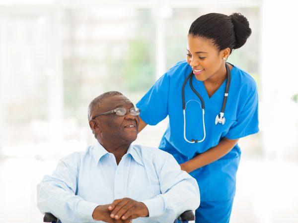 Man in rolstoel met verpleegster