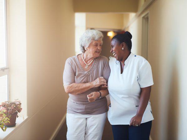 Vrouw en zorgkundige wandelen door de gang