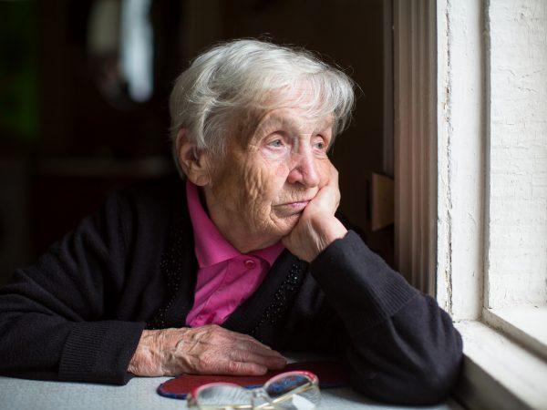 Verdrietige oude vrouw aan raam
