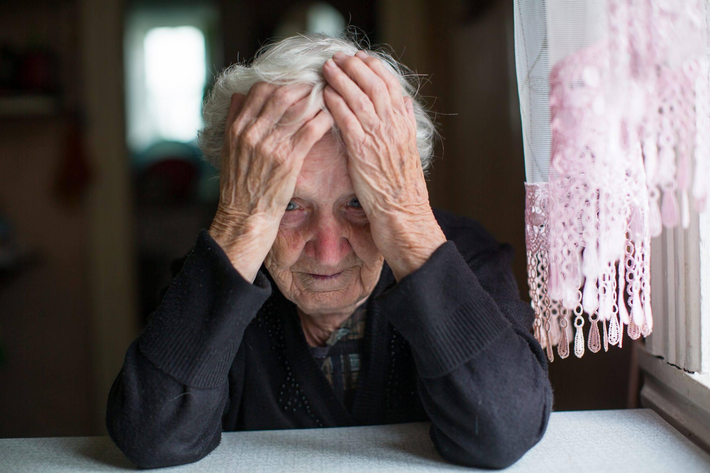 Oude vrouw met handen in het haar