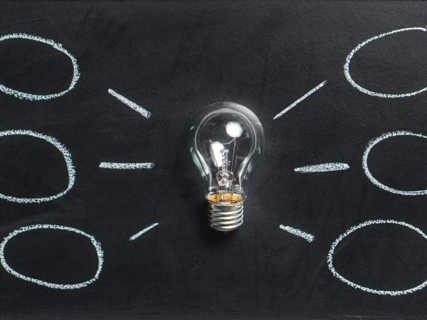 Gloeilamp op krijtbord met ideewolkjes